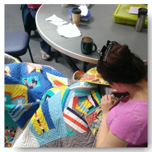 Amy hard at work binding the first of our Modern Block Challenge Quilts.  Quilting by Sandie