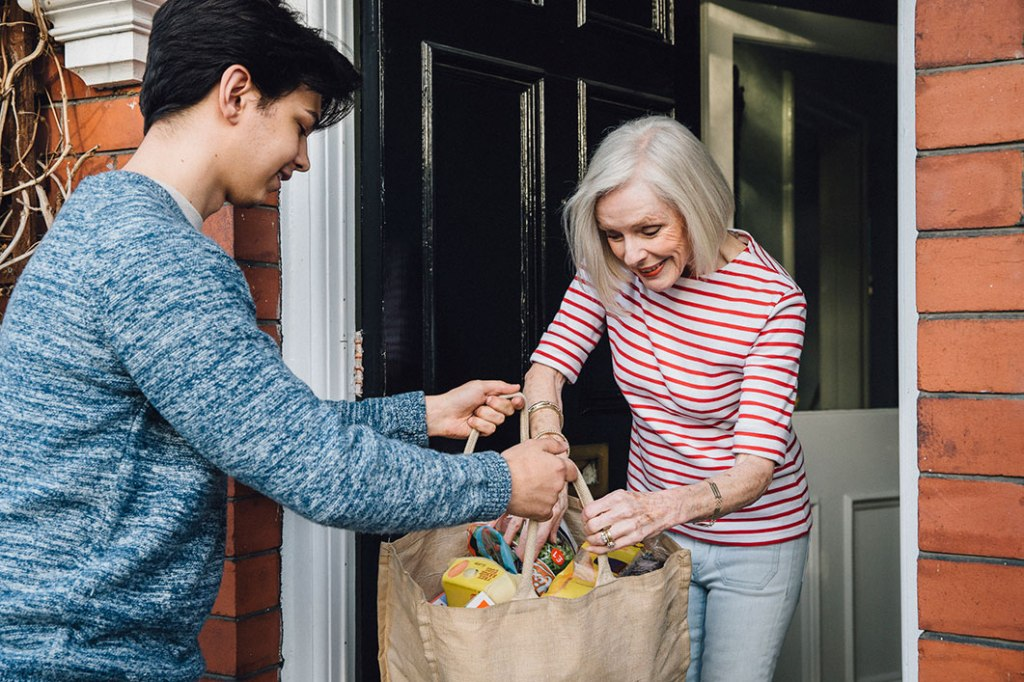 Young person delivering groceries to a senior woman